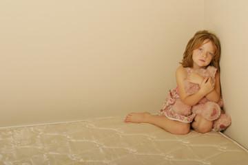 Sad girl sitting on an old mattress holding bear