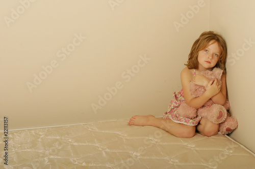 Sad girl sitting on an old mattress holding bear
