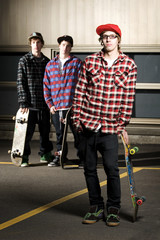 Three skateboarder kids standing in parking lot