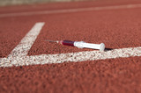 Doping syringe on athletics sports area poster