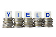 Stacks of coins with the word YIELD isolated on white background