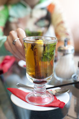woman taking a glass of tea with lemon, cinnamon stick, mint