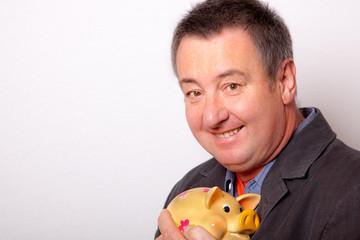 Mann freut sich über sein Sparschwein