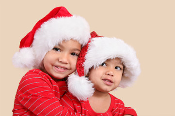 Two mixed race sisters in santa hats