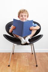 Young boy sitting in a chair reading a book