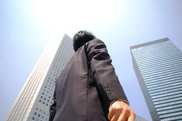 ビルを見上げるビジネスマン