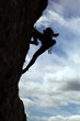 Silhouette of rock climber climbing a cliff