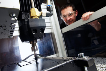man watching CNC machine in progress