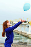 redheaded girl pushing balloon out