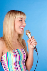 Cute young female singing song, isolated over blue