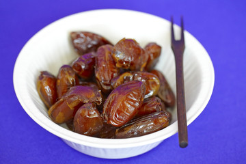 Bowl of date fruit with a wooden fork