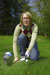 Woman golfer aiming for a swing with iron
