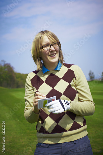 Golfer woman writing handicap and smiling