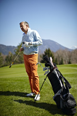 Man with a golf club and bag on the green
