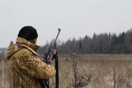Huner with rifle waiting for animal - 22221156