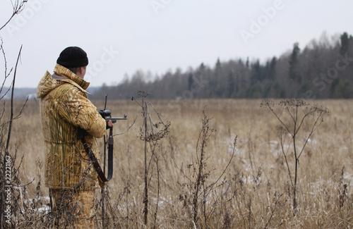 Huner with rifle waiting for animal - 22221167