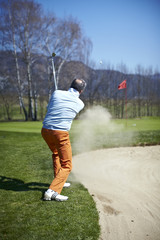 Golfer man at the bunker with sand and golf ball in the air