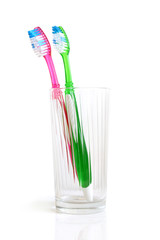 Two colorful tooth-brushes inside a glass