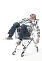 jeune homme dormant dans un caddie de supermarché