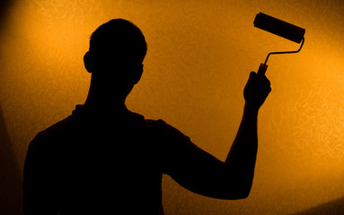 Back lit silhouette of man with paint-roller