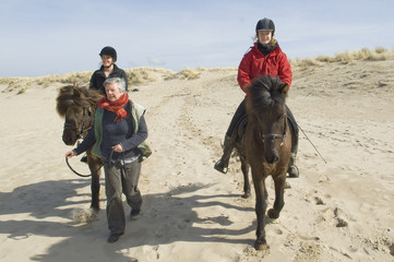 Two equestrians on horseback on the beach