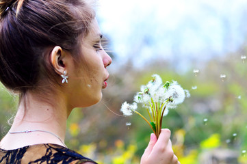 girl blowing on many dandelions