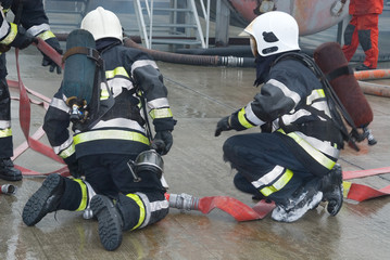 Fire fighters preparing hoses