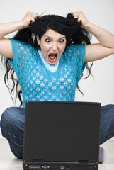 Frious woman with laptop  screaming