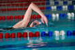 woman swims using the crawl stroke in indoor pool