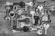 Old different keys on wooden board (black and white)