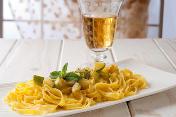 zucchinis pasta with mint and glass of white wine