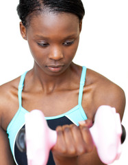 Serious woman working out with dumbbell
