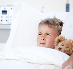 Sick little boy lying in a hospital bed