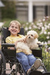 Young boy in wheelchair smiling and holding dog