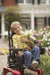 Young boy in wheelchair with flowers outdoors
