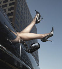 Woman's legs with high heels sticking out of car window