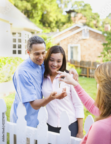 Woman handing key to couple in front of house