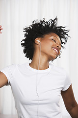 Close up of young African woman dancing to music on ear buds