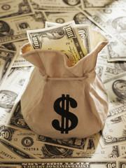 Bag of US Dollars on pile of US Dollars