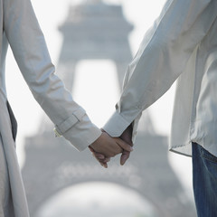 Couple holding hands in front of Eiffel Tower