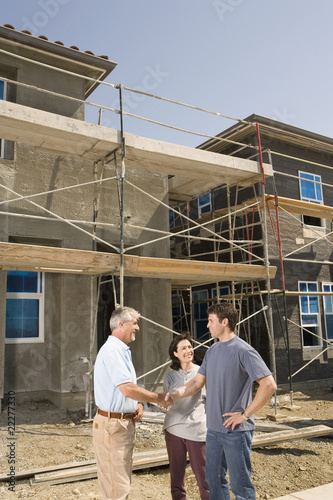 Man shaking hands with couple outside construction site