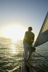 Man on sailboat looking at sunrise