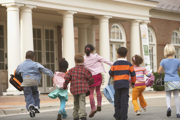 Multi-ethnic students running toward building