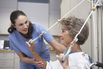 Senior female patient performing physical therapy with nurse