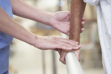 Close up of nurse assisting senior patient on railing