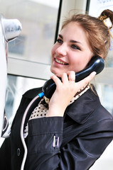 happy teen talking by public  telephone