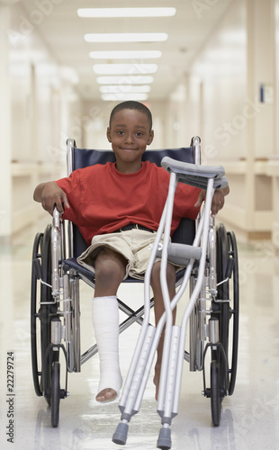 African boy with broken leg and crutches in wheelchair