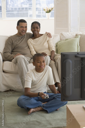 African family watching television in livingroom