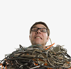 Studio shot of technician buried in computer cables