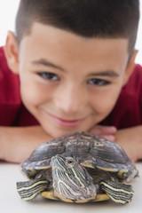 Close up of Hispanic boy and turtle